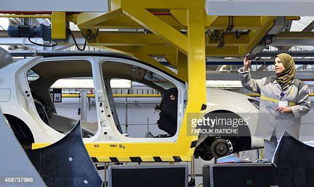 An employee of the French car maker Renault group takes a picture during the inauguration of a new production plant on November 10 in Oued Tlelat in...