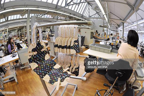 An employee of the French handbag compagny Louis Vuitton, part of world's biggest luxury group LVMH, works on hand-bags at the factory in...