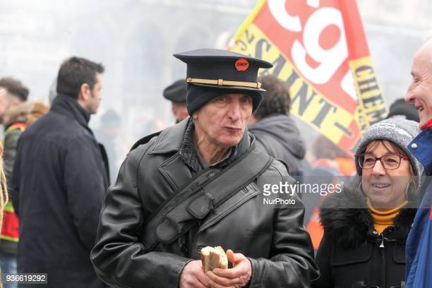 An employee of the French state owned railway company SNCF wearing a railroad employees cap demonstrates in front of the Gare de lEst railway station...