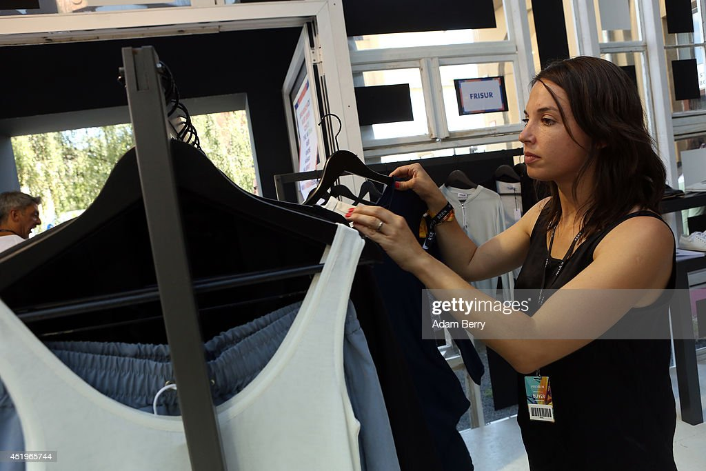 An Employee Of The Frisur Brand Stand Rearranges Clothing At The