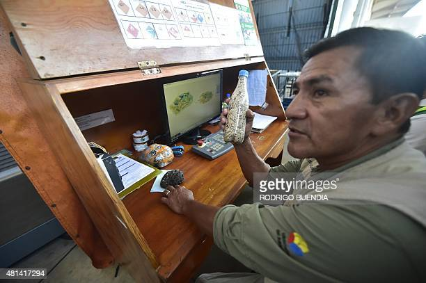 An employee of the Galapagos National Park shows a plastic bottle containing inorganic material confiscated from tourists at the airport in Baltra...
