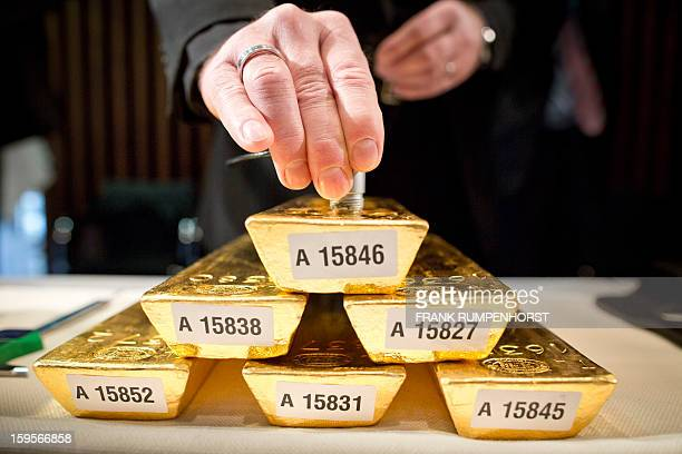 An employee of the German Federal Bank checks the core of a bar of gold during a press conference at the German Federal Bank in Frankfurt am Main...