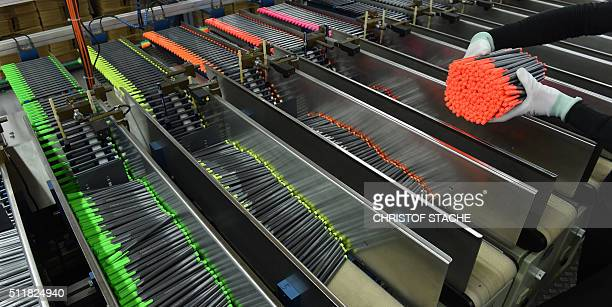 An employee of the German pencil maker Staedtler picks up the pencils out of a machine in a production hall of the company in Nuremberg southern...