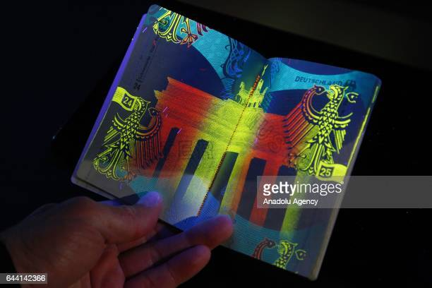 An employee of the Germany Interior Ministry shows the hologram security markings on the new German Passport during its presentation in the Ministry...