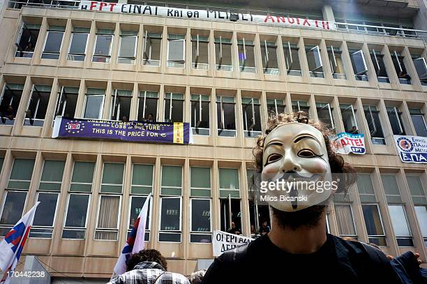 An employee of the Greek public broadcaster ERT wears a mask as he stands amongst other protesters while some of his colleagues stand at the windows...