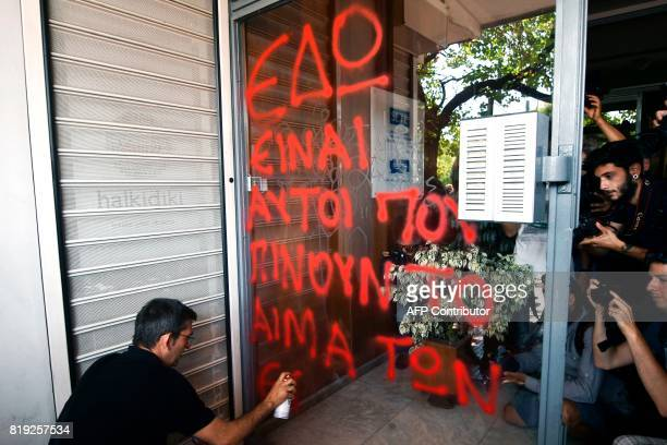 An employee of the Greek tourism sector sprays a slogan reading 'Here are these who suck the workers' blood' at the entrance of the Greek tourism...