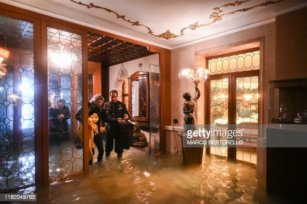 An employee of the Gritti Palace helps a customer walk across the flooded entrance during an exceptional Alta Acqua high tide water level on November...
