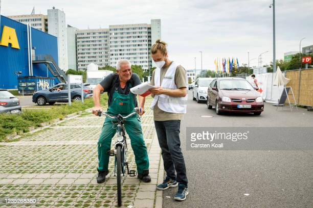 An employee of the health department instruct a cyclist about the Moderna vaccine in a drive-in vaccination station in an IKEA car park on the third...