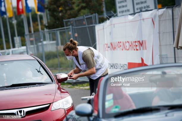 An employee of the health department instructs a car driver about the Moderna vaccine in a drive-in vaccination station in an IKEA car park on the...
