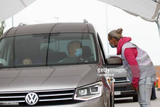 An employee of the health department instructs a driver about the Moderna vaccine in a drive-in vaccination station in an IKEA car park on the third...