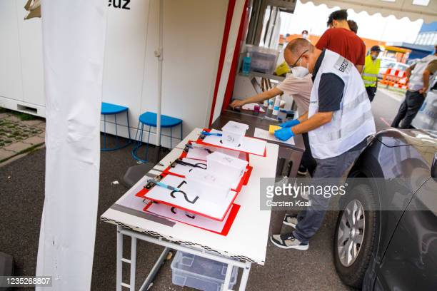 An employee of the health department prepares a dose of the Moderna vaccine in a drive-in vaccination station in an IKEA car park on the third day of...