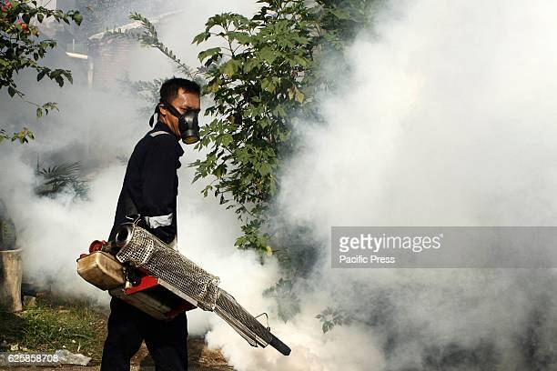 An employee of the Health Ministry sprays antimosquito fog in an attempt to control dengue fever at a neighborhood in Jakarta Indonesia Fogging is...