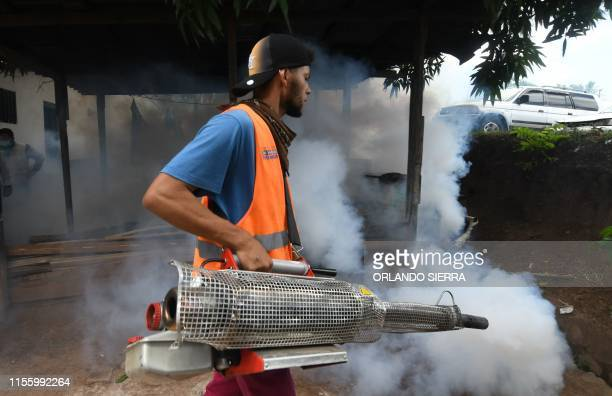 An employee of the Honduran Secretariat of Health takes part in a fumigation operation to combat Aedes aegypti vector of the dengue fever in...