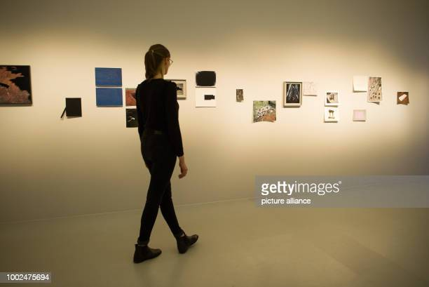 An employee of the House of Photography looks at a photograph of the exhibition 'Umbra' of the Dutch photographer Viviane Sassen in Hamburg Germany...