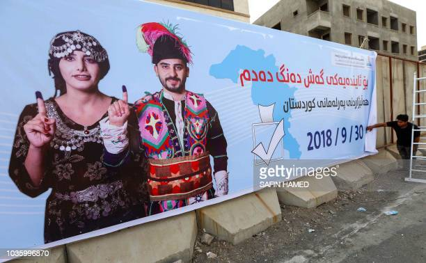 An employee of the Independent High elections and Referendum Commission of the northern Iraqi Kurdistan autonomous region hangs up a poster...