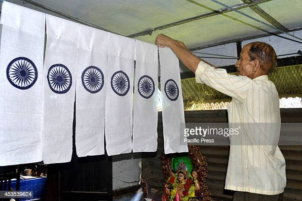 An employee of the Indian Khadi and Gramadyug company prepares the Indian Tricolored National Flags ahead of the Indian Independence day in a...