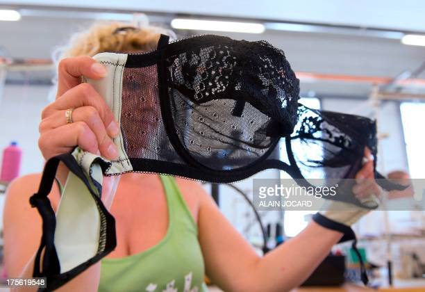 """An employee of the """"Indiscrete"""" lingerie brand checks a bra on July 1, 2013 at the company's production site in Chauvigny, centralwestern France. The..."""