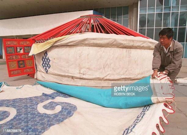 An employee of the Inner Mongolia Hohhot Wood Furniture Factory dismantles a Mongolian yurt at a real estate exhibition in Beijing 07 May Selling for...