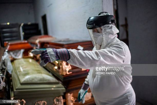 An employee of the Iztapalapa pantheon works during the cremation of a victim of COVID-19 in Mexico City, on June 11 amid the novel coronavirus...