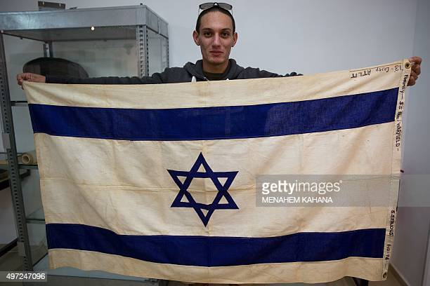 An employee of the Kedem Auction House in Jerusalem on November 15 2015 shows the flag of the iconic ship the SS Exodus the most famous of hundreds...
