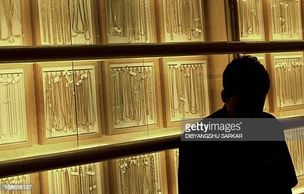 An employee of the Lalithaa jewellery shop stands in front of a necklace display in Madras 22 April 2004 during Akshaya Tritiya the third day of the...