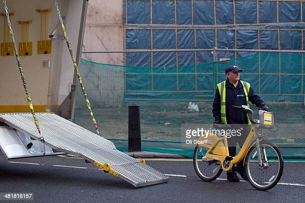 An employee of the London Cycle Hire scheme maneuvers a specially painted yellow bike into a transport lorry on April 1 2014 in London England 101 of...
