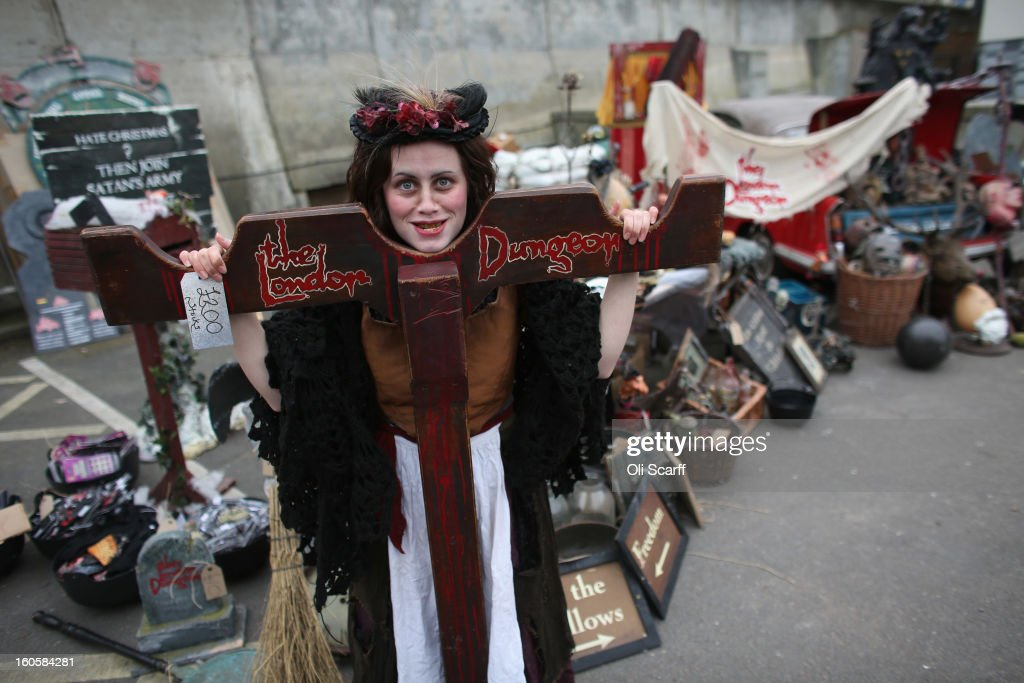 An employee of 'The London Dungeon' poses with props previously used at the attraction which are to be sold at a car boot sale in Pimlico as the Dungeon prepares to move to new premises on the Southbank, on February 3, 2013 in London, England. The sale features a selection of torture and surgical implements, costumes, plague doctor's potions, false eyeballs, severed limbs, and a set of stocks. The London Dungeon will reopen in March 2013 in larger premises on the Thames' Southbank, having moved from Tooley Street where it originally opened 38 years ago.