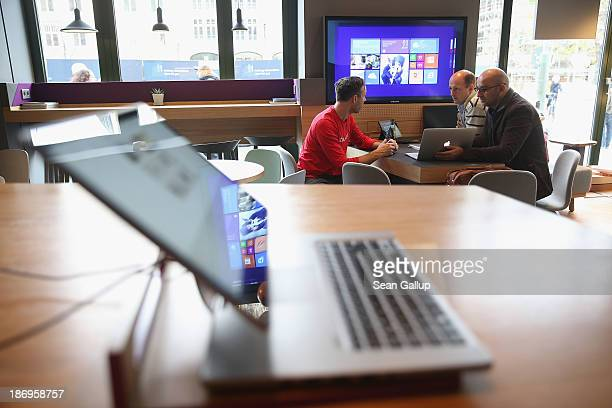 An employee of the Microsoft Digital Eatery chats with customers at the Microsoft Digital Eatery cafe on November 5 2013 in Berlin Germany The...