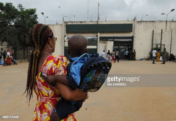 An employee of the Mireille Hanty foundation carries Emmanuel a two and a half yearold boy in front of the prison he lives in on the day he attended...