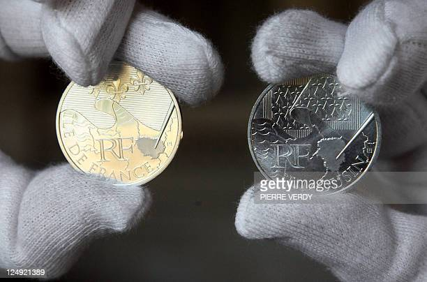 An employee of the Monnaie de Paris presents on September 16 2010 at the Monnaie de Paris two 10euro coins from a new limited collection of coins...