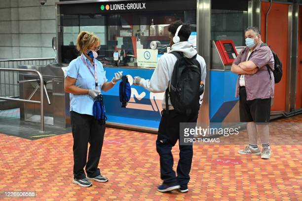 An employee of the Montreal metro offers free masks to traveller who don't have one with them at the Lionel Groulx station on July 13, 2020 as face...
