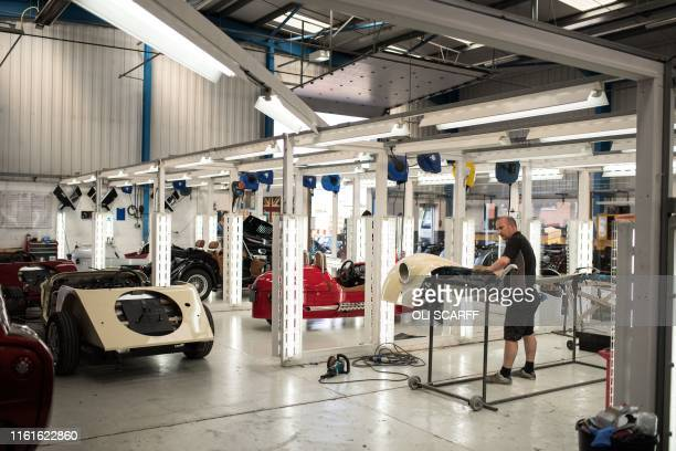 An employee of The Morgan Motor Company checks and polishes a car wing section in an inspection bay at the car firm's factory in Malvern southwest of...