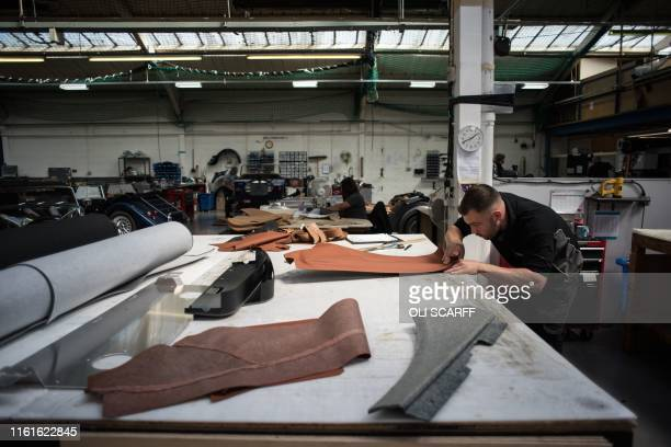 An employee of The Morgan Motor Company works to produce leather door covers in the trim shop of the car firm's factory in Malvern southwest of...