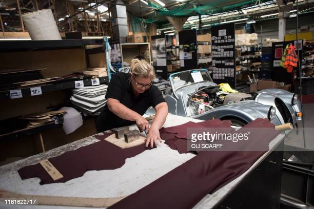 An employee of The Morgan Motor Company works to produce leather headrest covers in the trim shop of the car firm's factory in Malvern southwest of...