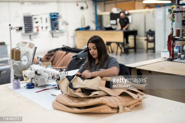 An employee of The Morgan Motor Company works to produce leather seat covers in the trim shop of the car firm's factory in Malvern southwest of...