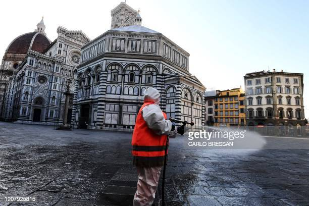 An employee of the municipal company disinfects Piazza del Duomo, in Florence, on March, 21 2020, as part of the measures taken by Italian government...