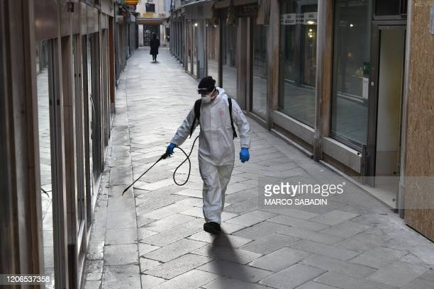 TOPSHOT An employee of the municipal company Veritas sprays disinfectant in public areas in Venice on March 11 as part of precautionary measures...