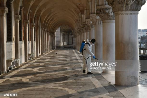 An employee of the municipal company Veritas sprays disinfectant in public areas by the arcades of the Doges' Palace in Venice on March 11 as part of...
