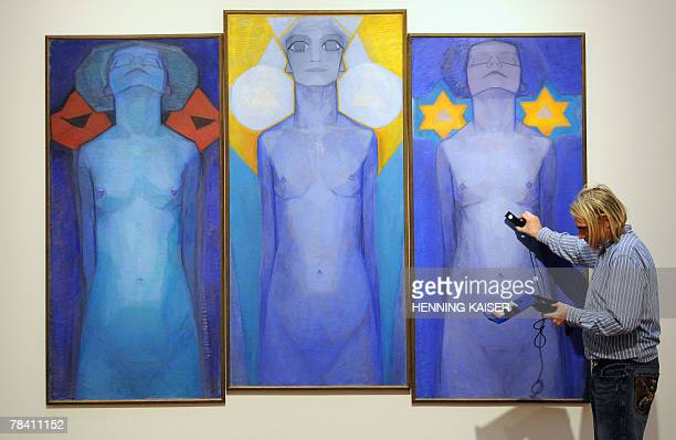 An employee of the Museum Ludwig measures the lighting strength at the painting 'Evolution' by Dutch artist Piet Mondrian shown in the exhibition...