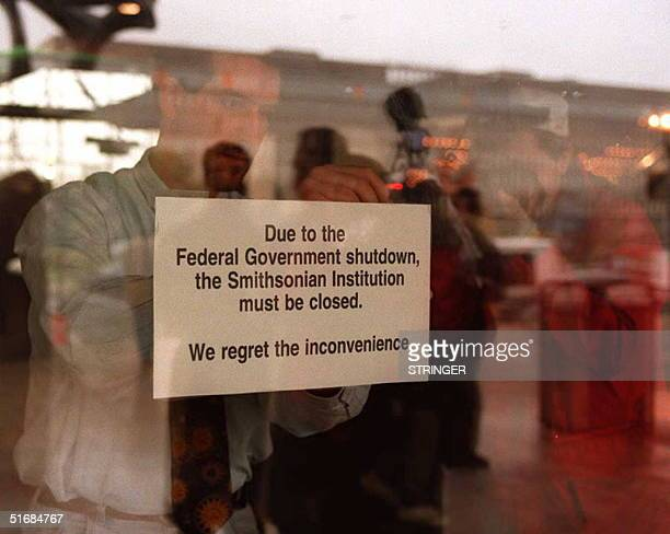An employee of the National Air and Space Museum in Washington, DC hangs a sign on the door 14 November explaining the reason for the museum closure....