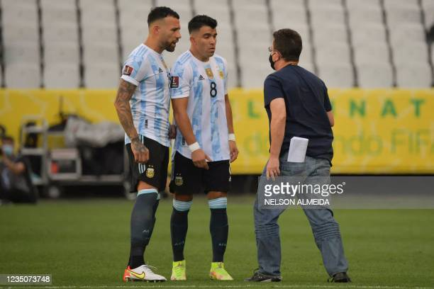 An employee of the National Health Surveillance Agency argues with Argentina's Nicolas Otamendi and Argentina's Marcos Acuna during the South...