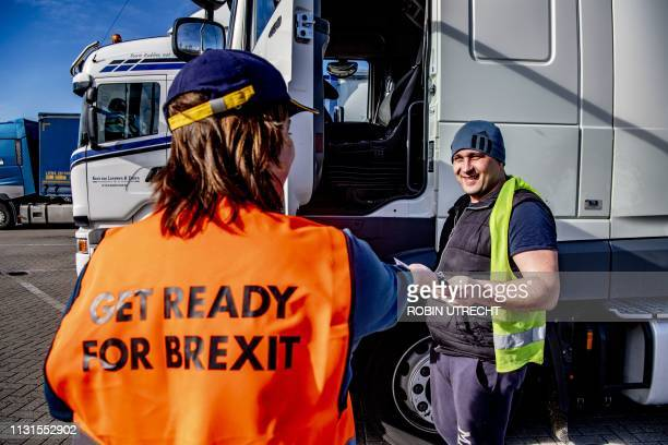 An employee of the Port of Rotterdam hands out flyers with information about Brexit to a truck driver at the entrance of the Stena terminal in the...
