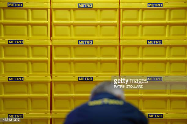 An employee of the retail and wholesale/cash and carry group Metro caries and sorts products in a market in Cologne Germany on December 12 2013 AFP...