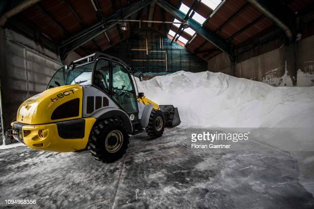 An employee of the road maintenance depot works with a wheel loader in a salt storage on February 07 2019 in Birkenwerder Germany