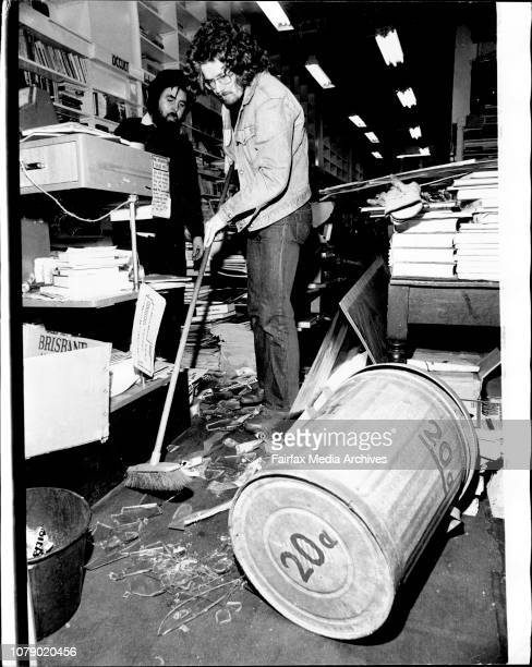 An employee of the shop Dale Keeling is pictured clean up broken glass in the front part of the premises The garbage can used in the incident is in...