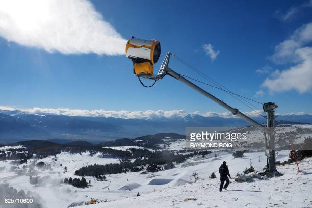 An employee of the ski resort of FontRomeu southern France controls a snow gun on November 25 2016 prior to the opening of ski hills / AFP / RAYMOND...