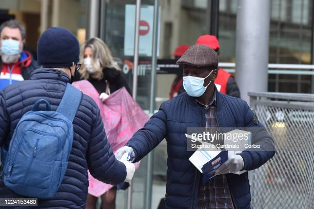 An employee of the SNCF wearing a protective face mask distributes free face masks to people arriving at Gare du Nord railway Station in Paris on May...