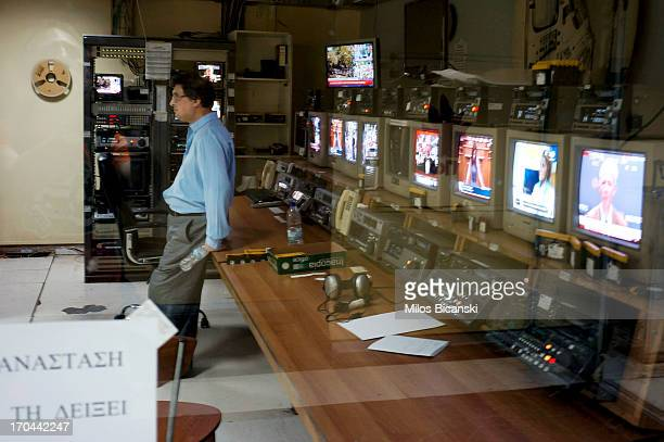 An employee of the state broadcaster ERT leans against a desk in a control room during an online news bulletin broadcast at the corporation's...