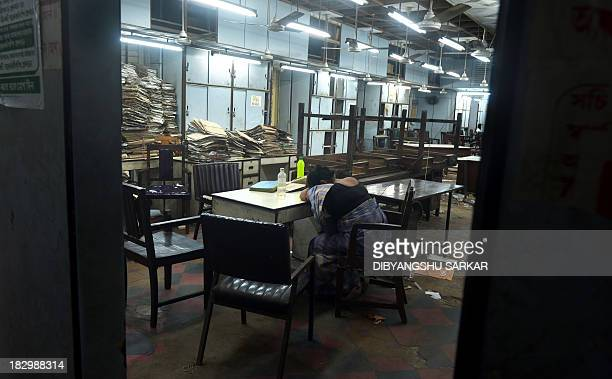 An employee of the state government of West Bengal takes a nap in the empty office at the state secretariat building called Writer's Building in...
