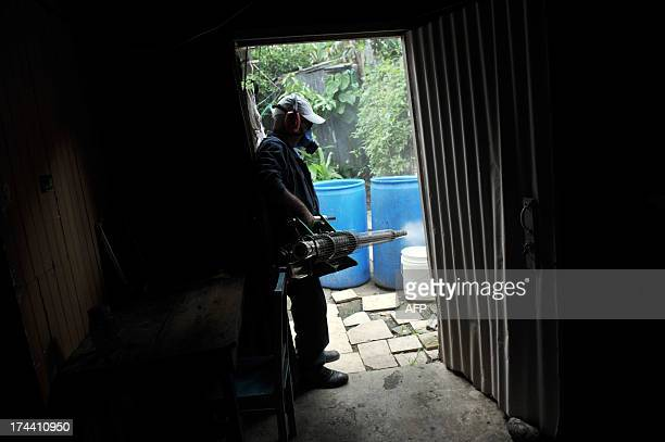 An employee of the Technical Vector Unit Health Monitoring fumigates a house to eliminate potential breeding sites of dengue mosquitoes Aedes aegypti...